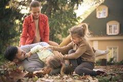 Маленькие девочки играя с родителями, девушки щекоча отца стоковые изображения rf