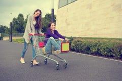 Маленькие девочки имеют потеху с вагонеткой покупок Стоковые Изображения RF