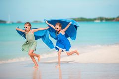 Маленькие девочки имея потеху на тропическом пляже играя совместно Прелестные маленькие сестры на пляже во время летних каникулов стоковое изображение rf