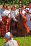 Маленькие девочки наслаждаются сыграть музыкальный инструмент во время латышского внешнего фольклорного фестиваля на поле Turaida Стоковые Изображения RF