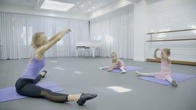 Маленькие девочки на балете классифицируют с учителем женщины в школе внутри помещения сток-видео