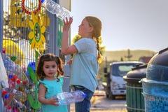 Маленькие девочки повторно используя пластиковые бутылки с водой Клеть пластиковых бутылок с водой готовых для повторно использов стоковое фото
