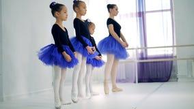 Маленькие девочки протягивают ноги после их инструктора дамы сток-видео