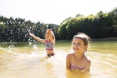 Маленькие девочки стоя в озере лето солнечное Стоковое Изображение