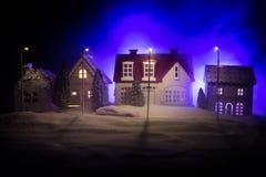 Маленькие декоративные дома, красивый праздничный натюрморт, милые небольшие дома на ноче, предпосылке bokeh города ночи реальной стоковые фото