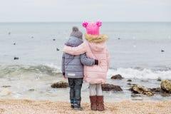 Маленькие дети стоят в объятии на пляже Стоковые Фотографии RF