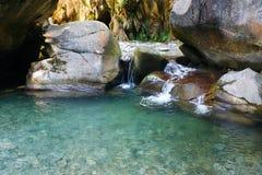 Маленькие дивные освежая водопады среди утесов заводи горы стоковое изображение rf