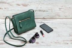 Маленькие зеленые дамы сумка, солнечные очки, губная помада и умный phon Стоковая Фотография