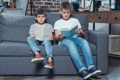 маленькие кавказские книги чтения мальчиков пока сидящ на софе Стоковое Изображение