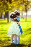 Маленькие милые девушки имея потеху внешнюю 2 милых девушки стоят на зеленой траве и обнимать Стоковые Фото