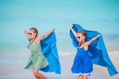Маленькие милые девушки имея потеху на белом пляже Стоковое Изображение