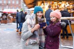 Маленькие милые дочь и мать с чашкой испаряться пунш горячего шоколада или детей Счастливые девушка ребенка и красивый стоковые изображения rf