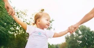 Маленькие милые руки взятия девушки с ее людьми родственников стоковое изображение