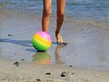 Маленькие небольшие ноги ребенка в воде на песчаном пляже ослабляя и стоя с красочным шариком во время летних каникулов стоковая фотография