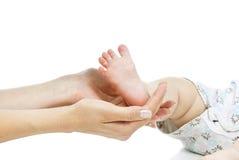 Маленькие ноги младенца и руки мати стоковые изображения