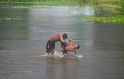 Маленькие ребеята играя в пруде мочат уникально фото стоковое изображение