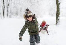Маленькие ребеята наслаждаются ездой саней Sledding ребенка Игра детей outdoors в снеге Стоковые Изображения