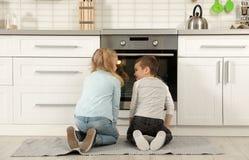 Маленькие ребята ждать подготовку плюшек в печи дома стоковое изображение
