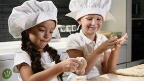 Маленькие ребята играют вожди с тестом, вращающей осью и мукой 5-6 - летняя деятельность совместно в рисбермах и шляпах шеф-повар видеоматериал