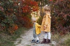 Маленькие ребята идут в лес осени в ретро платьях стоковые изображения rf