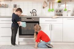 Маленькие ребята печь плюшки в печи стоковая фотография