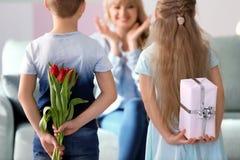 Маленькие ребята пряча подарки для матери за их задними частями дома стоковые фотографии rf
