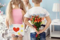 Маленькие ребята пряча подарки для матери за их задними частями дома стоковые изображения