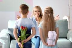 Маленькие ребята пряча подарки для матери за их задними частями дома стоковое изображение rf