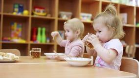 Маленькие ребята сидят на таблице, одном из их выпивают что-то от чашки, другое одно все еще едят что-то от видеоматериал