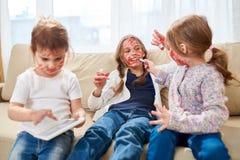 Маленькие сестры играя с красной губной помадой стоковое изображение rf