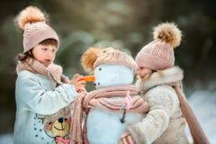 Маленькие сестры с снеговиком стоковое фото