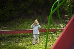 Маленькие счастливые рыжеволосые бега девушки на отрезанной зеленой траве в парке детей под приятным солнцем стоковая фотография rf
