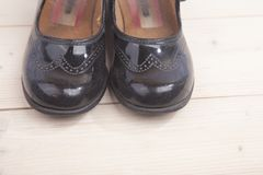 Маленькие черные ботинки на деревянной предпосылке стоковое изображение rf