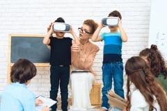 Маленькие школьники получают знакомыми с технологией виртуальной реальности стоковое изображение