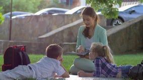 Маленькие школьники слушая женскую читая книгу потехи сидя на зеленой лужайке в природе в солнечном свете после школы акции видеоматериалы