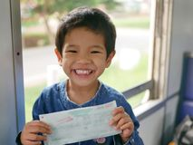 Маленький азиатский младенец держа билет на поезд в ее руках с большой счастливой улыбкой пока она путешествует поездом в первый  стоковое изображение