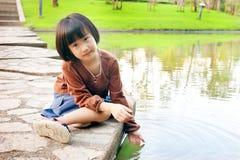 Маленький азиатский ребенок играя на воде от дока озера стоковая фотография