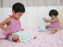 Маленький азиатский ребёнок вышел учить сложить одежды стоковые изображения rf