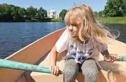 Маленький белокурый rowing девушки на шлюпке Стоковые Изображения RF