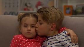 Маленький брат и сестра обнимая, мальчик целуя девушку на заботе щеки, замедленном движении видеоматериал