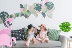 Маленький брат и сестра сидят на софе в комнате ` s детей стоковая фотография