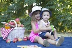 Маленький брат и сестра сидя на траве в парке близко стоковые фотографии rf