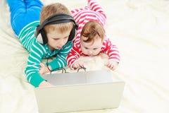 Маленький брат и сестра с компьтер-книжкой дома стоковые изображения