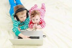 Маленький брат и сестра с компьтер-книжкой дома стоковое изображение