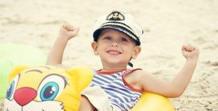 Маленький кавказский мальчик в костюме матроса и крышка сидя на пляже в заплыве звенят и смех Стоковые Изображения RF