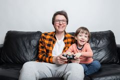Маленький красивый мальчик и его папа сидят на кресле дома и играют видеоигры с кнюппелем Папа и сын имеют потеху стоковые фото