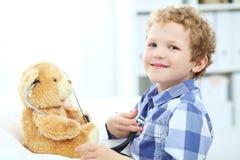 Маленький курчавый кавказский мальчик играет в докторе с стетоскопом и плюшевым медвежонком Стоковое Изображение