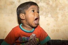 Маленький мальчик попрошайки от Индии стоя на streetside, плача для еды стоковые фото