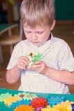 Маленький милый кавказский мальчик соединяет части ` s конструктора рядом с горой покрашенных деталей Игры мальчика в Стоковые Фото