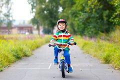 Маленький милый мальчик ребенк на велосипеде на лето или день autmn Здоровый счастливый ребенок имея потеху с задействовать на ве стоковое фото